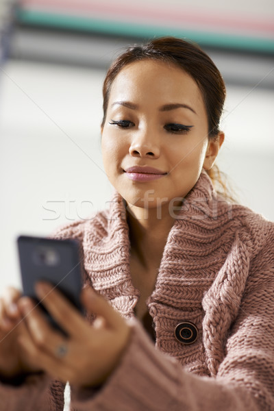 asian girl reading sms on smarthphone Stock photo © diego_cervo