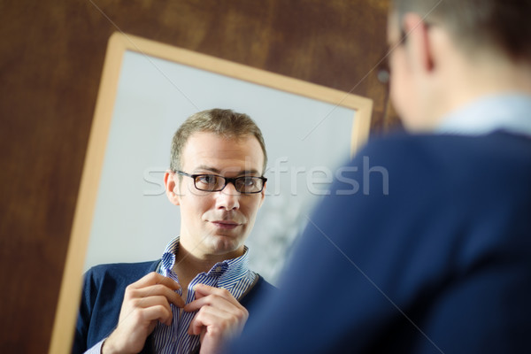 Young man dressing up and looking at mirror Stock photo © diego_cervo