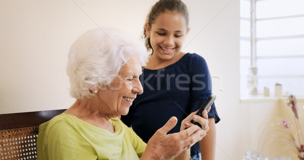 Girl Helps Old Woman Using Mobile Phone And Technology Stock photo © diego_cervo