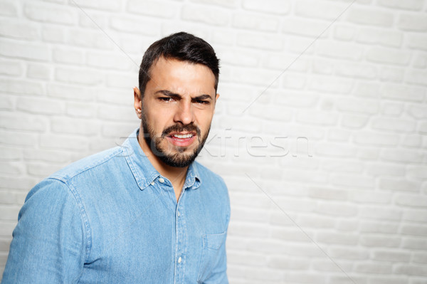 Facial Expressions Of Young Beard Man On Brick Wall Stock photo © diego_cervo