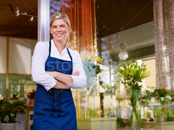 Young pretty woman working as florist in shop and smiling Stock photo © diego_cervo