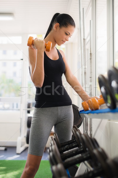 Young latina woman taking weights from rack in fitness club Stock photo © diego_cervo