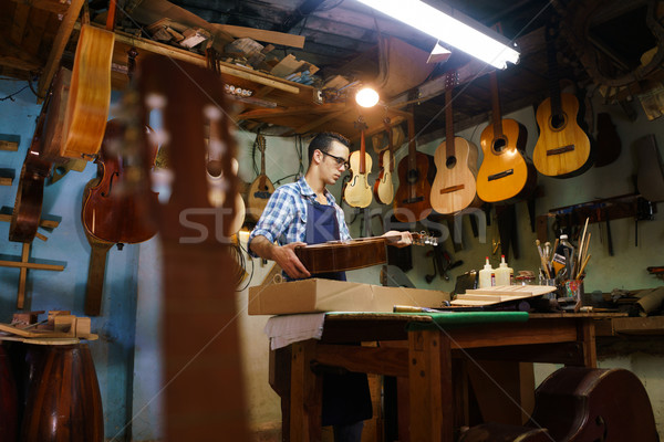 Stock photo: Artisan Lute Maker Storing Guitar Music Instrument In Case For C