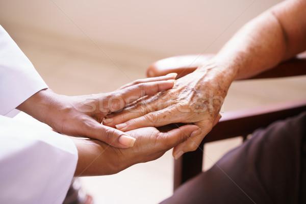 Idős nő beszél fekete orvos elfekvő Stock fotó © diego_cervo
