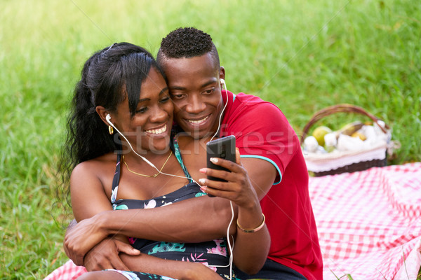 Couple Listening To Music And Watching Video On Mobile Phone Stock photo © diego_cervo