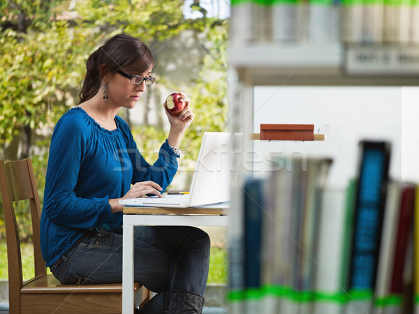 girl holding apple in library Stock photo © diego_cervo