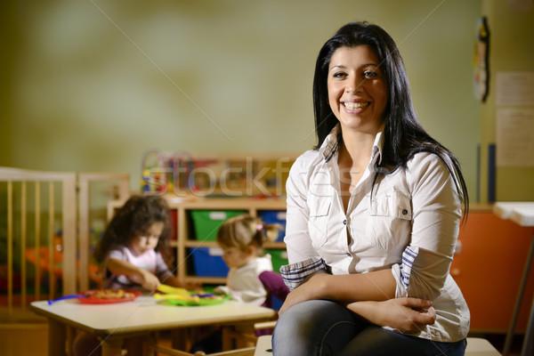 happy teacher with children eating in kindergarten Stock photo © diego_cervo