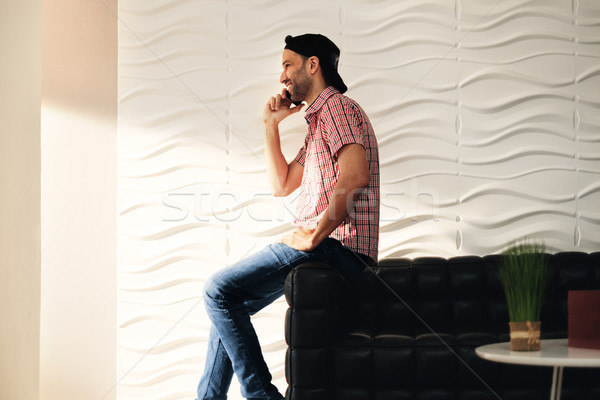 Young Latino Man Talking On Cell Phone At Home Stock photo © diego_cervo