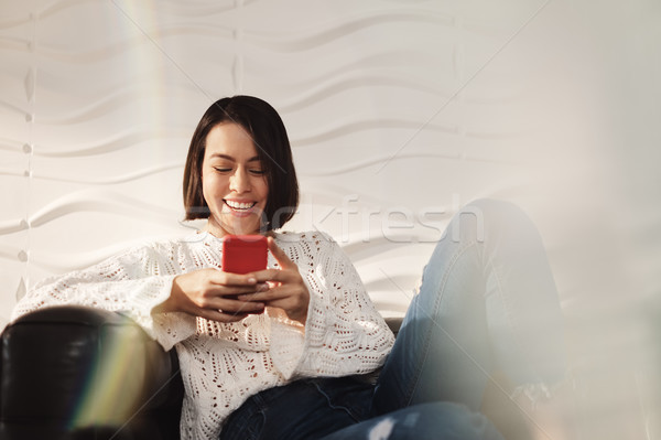 Jonge latino meisje messaging mobiele telefoon sofa Stockfoto © diego_cervo