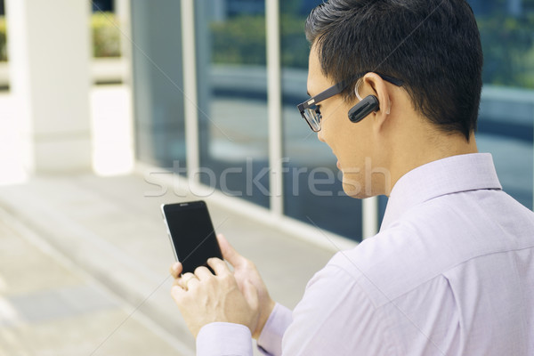 Businessman Calling On Mobile Phone With Bluetooth Handsfree Stock photo © diego_cervo