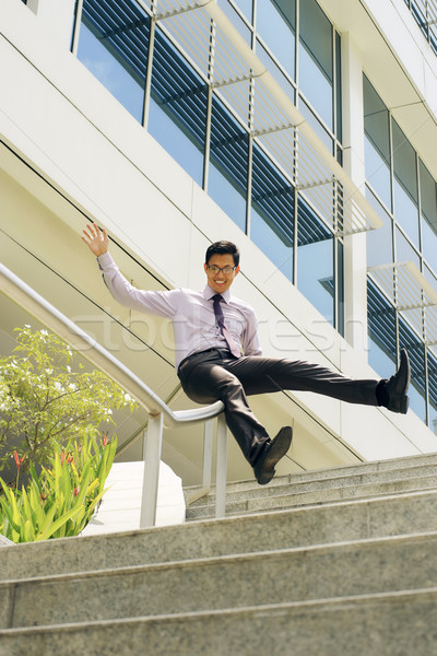 Happy Chinese Businessman Going Downstairs Sliding On Rail Stock photo © diego_cervo