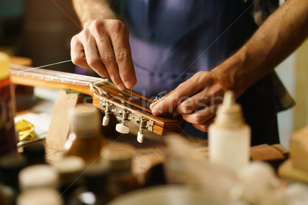 Stock photo: Artisan Lute Maker Fixing Stringed Instrument Replacing Guitar C