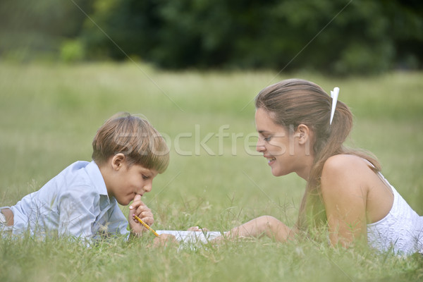 Mom helping son with homework, laying down on grass Stock photo © diego_cervo