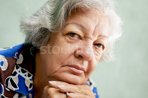 Portrait of serious old woman looking at camera with hands on ch Stock photo © diego_cervo