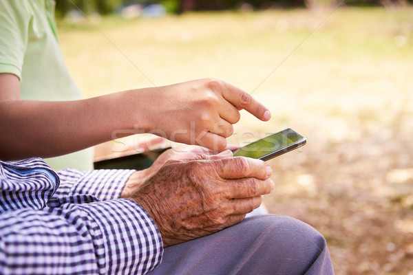 Child Helping Old Grandfather With Mobile Phone And Internet Stock photo © diego_cervo
