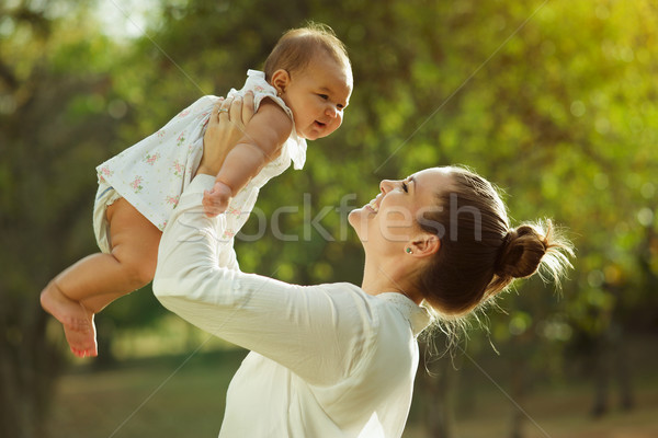 Stock photo: Mother Lifting Up And Turning Around Little Baby Daughter In Par