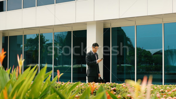 Businessman Chatting On Mobile Phone Walking To Office Stock photo © diego_cervo