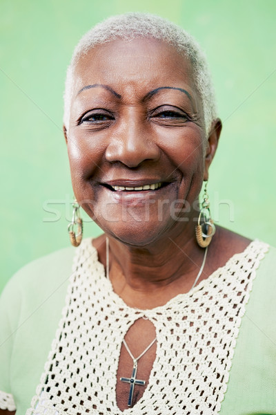 Portrait of senior black woman smiling at camera on green backgr Stock photo © diego_cervo