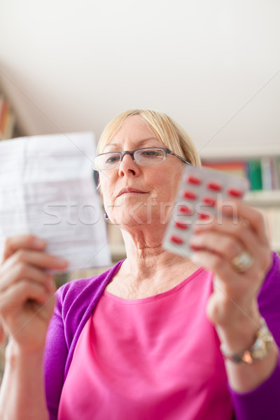 Senior woman with medication pills and prescription Stock photo © diego_cervo