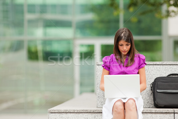 Stock photo: businesswoman using laptop outdoors