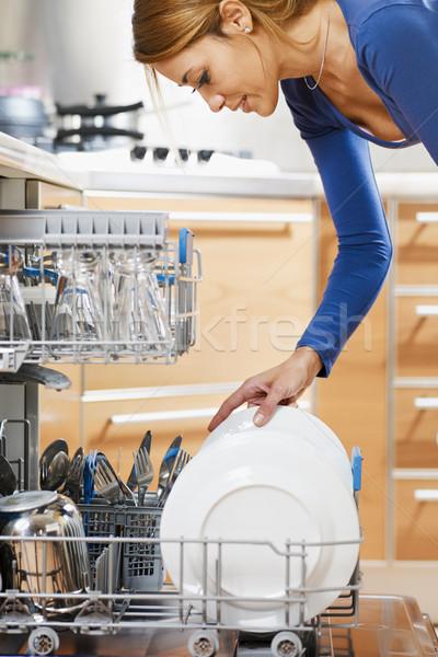 Kadın bulaşık makinesi yandan görünüş genç kadın mutfak gülümseme Stok fotoğraf © diego_cervo