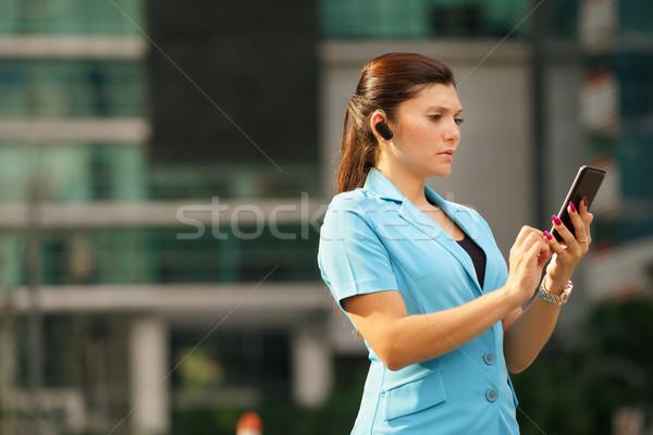 Femme d'affaires coup de téléphone bluetooth appareil adulte Photo stock © diego_cervo