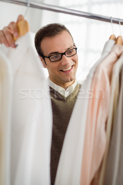Stock photo: adult man choosing shirt in clothes shop