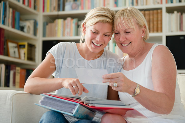 Mother and daughter looking at pictures in photo album Stock photo © diego_cervo