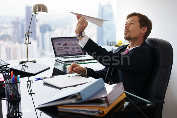 Bored White Collar Worker Throwing Paper Airplane In Office Stock photo © diego_cervo