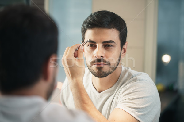 Latino Man Trimming Eyebrow For Body Care In Bathroom Stock photo © diego_cervo