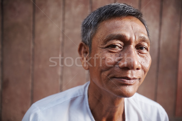 asian old man looking at camera against brown wall Stock photo © diego_cervo