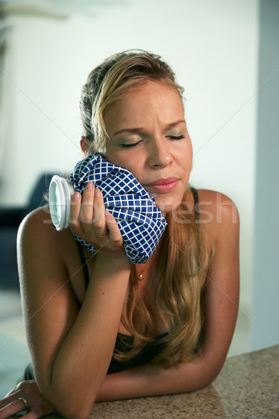Young woman with toothache holding ice bag on mouth Stock photo © diego_cervo