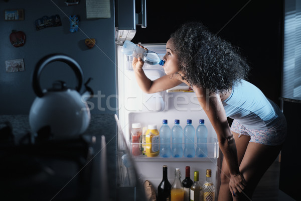 Stock photo: Black Woman Sweating And Drinking Water At Night