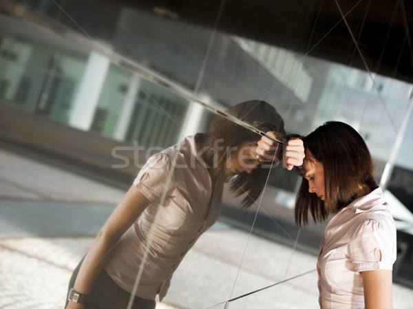 Stock photo: frustrated woman banging head against wall of office building