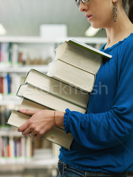 woman holding pile of books in library Stock photo © diego_cervo