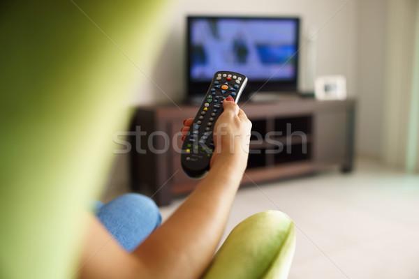 Kadın kanepe izlerken tv kanal uzak Stok fotoğraf © diego_cervo