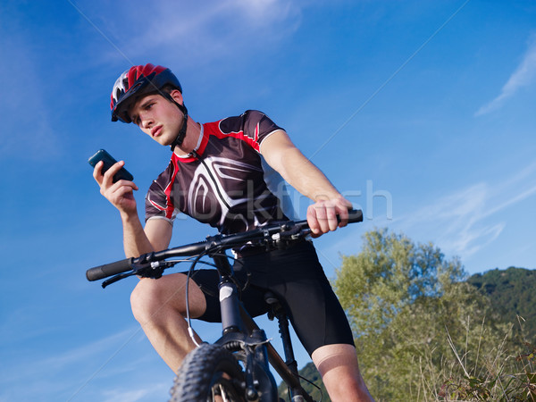 Jonge man telefoon paardrijden mountainbike sport activiteit Stockfoto © diego_cervo