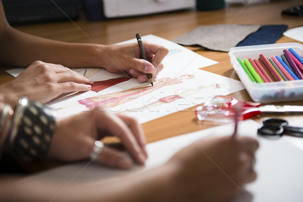 Stock photo: female fashion designers drawing new dress in studio