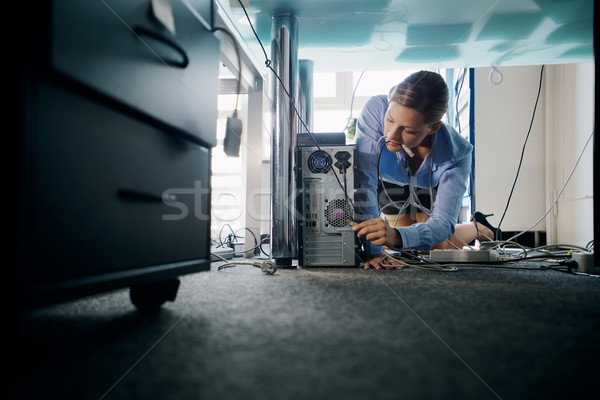 Young secretary connecting cables to pc in office Stock photo © diego_cervo