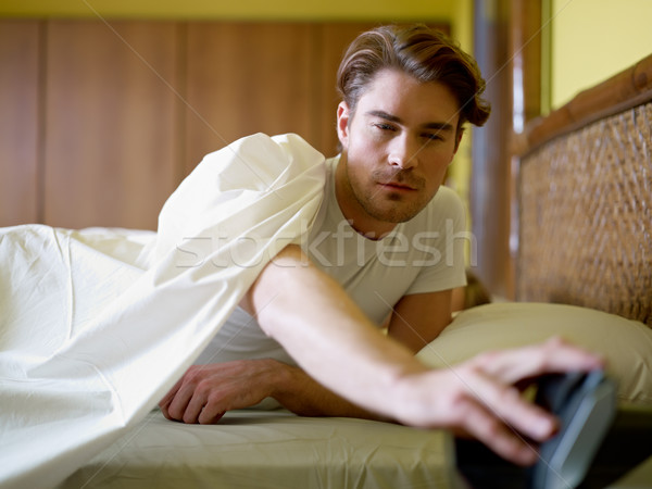 Stock photo: young adult man waking up in the morning