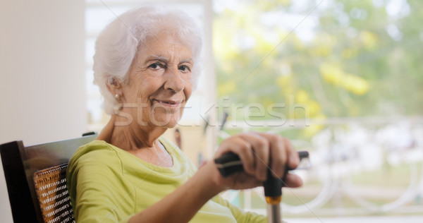 Portrait Old Lady Sitting On Rocking Chair Holding Stick Stock photo © diego_cervo