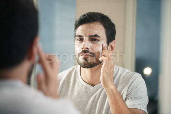Young Man Applying Anti-aging Lotion fot Skin Care Stock photo © diego_cervo