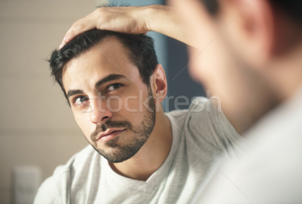 Man Worried For Alopecia Checking Hair For Loss Stock photo © diego_cervo