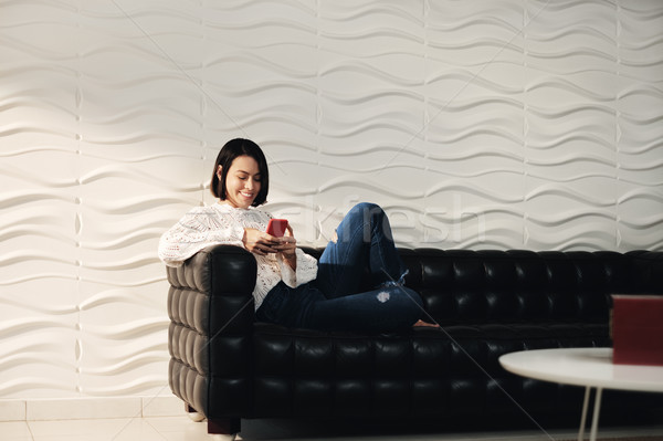 Jovem hispânico menina mensagens celular sofá Foto stock © diego_cervo