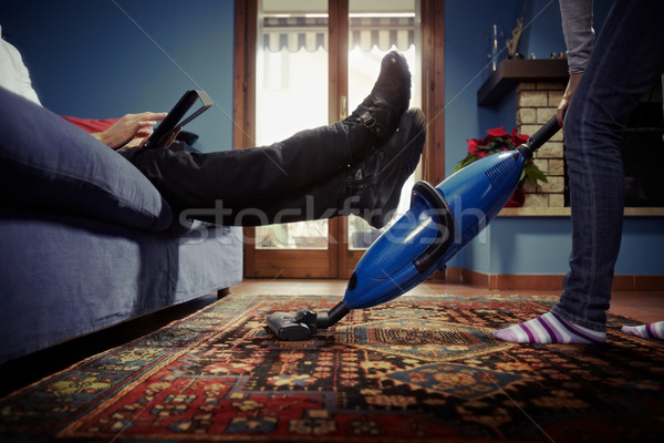 man relaxing while woman doing chores at home Stock photo © diego_cervo