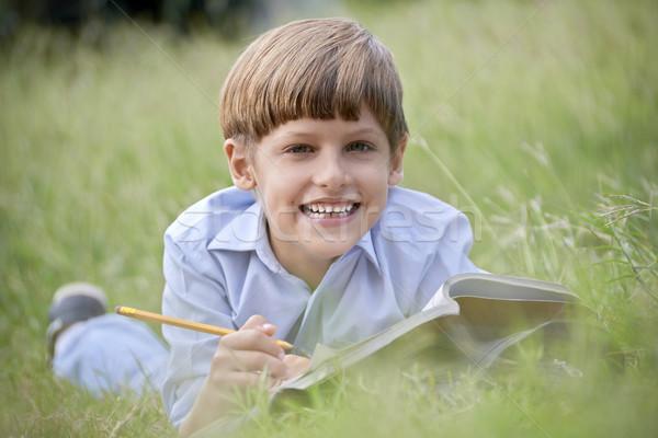Szczęśliwy praca domowa uśmiechnięty trawy młodych ludzi Zdjęcia stock © diego_cervo