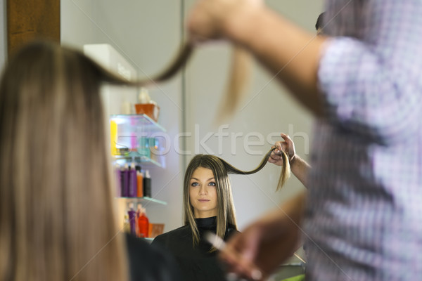 Stock photo: woman in hairdresser shop cutting long hair