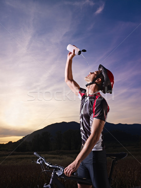 portrait of man training on mountain bike at sunset Stock photo © diego_cervo