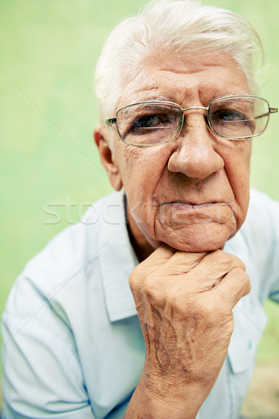 Portrait of serious old man looking at camera with hands on chin Stock photo © diego_cervo
