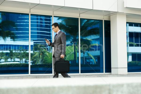 üzletember olvas email mobiltelefon sétál iroda Stock fotó © diego_cervo